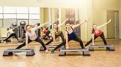 Group of women making step aerobics in the fitness class poster