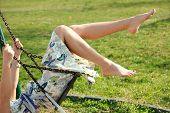barefoot young woman in dress on swing outdoor in park warm spring day poster