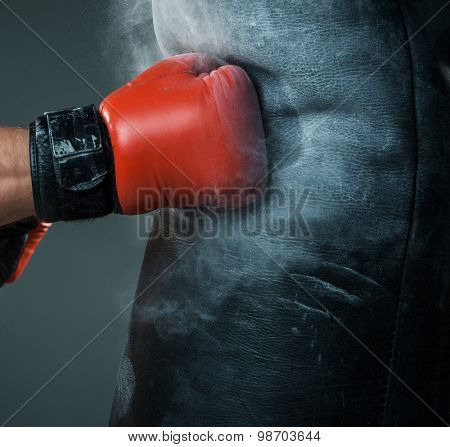 Close-up hand of boxer at the moment of impact on punching bag over black background poster