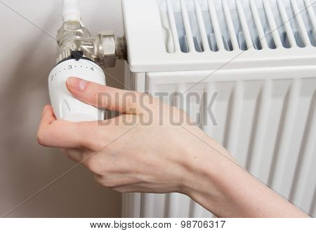 Closeup of a radiator thermostat with woman hand poster