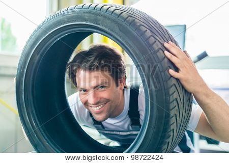 Auto mechanic changing tire in car workshop poster