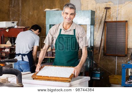 Portrait of smiling male worker dipping mold in pulpy water while coworker working at paper factory