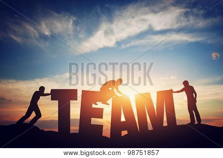 People connect letters to compose the team word. Teamwork concept, idea. Sunset positive light.