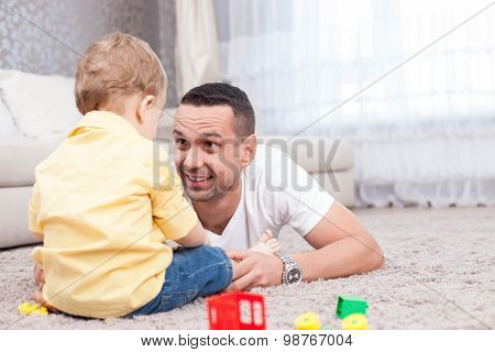 Cheerful young man is spending time with his child