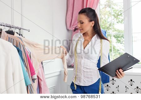 Cheerful young clothes designer is checking her collection