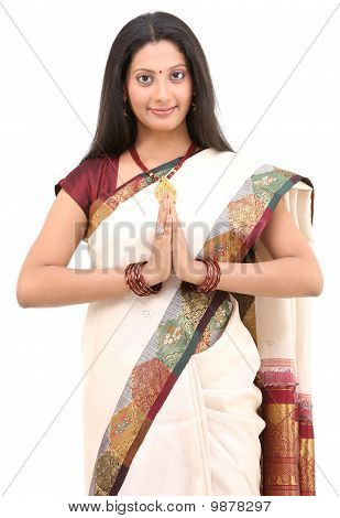 Woman in white sari posing welcome posture