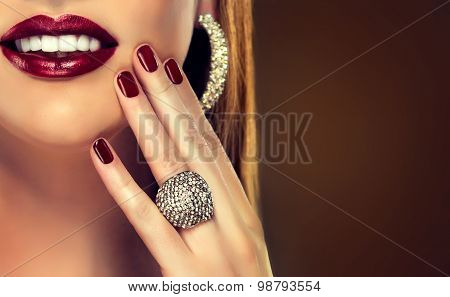 girl with straight hair and red manicure . A beautiful smile with white straight teeth