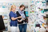 Smiling female chemist holding eye drops while customer using digital tablet in pharmacy poster