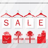 Clothing hangers SALE signage and banners with gift boxes and gift bags behind shopping window poster