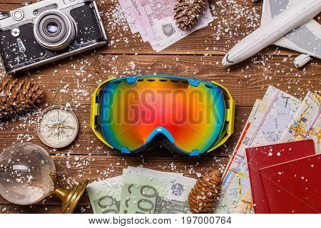 Photo of money, snow, passports, snowboarder glasses, plane globe on wooden background