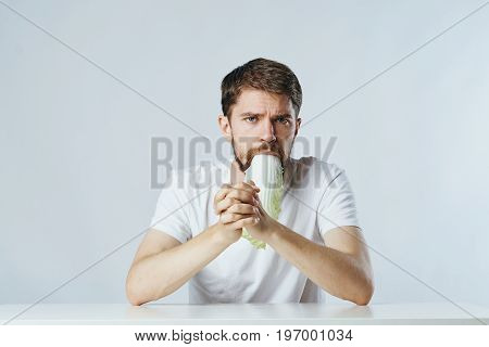 Man with beard on white isolated background eating salad, vegetables, diet, vegetarian.