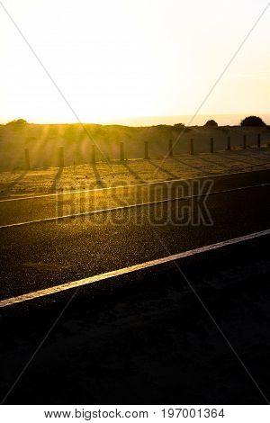 Coast asphalt road. Sunrise on asphalt coat, macro photo of road. Beach. Highway in Spain.