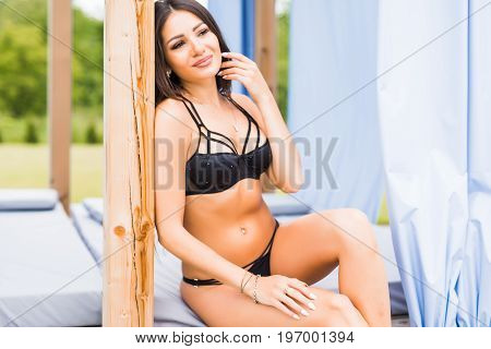 Happy Young Woman In Swimsuit Laying On Chaise-longue Poolside. Summer