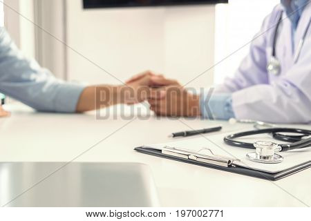 Focus of Medical instruments stethoscope and doctor touching patient hand for encouragement and empathy on the hospital blurred background Bad news.