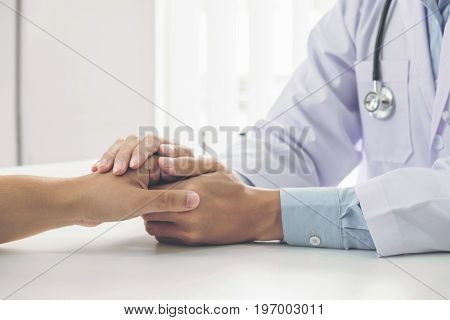 Close up of doctor touching patient hand for encouragement and empathy on the hospital cheering and support patient Bad news medical examination trust and ethics