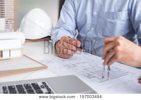 Engineering or Creative architect in construction project Engineers hands working with compasses on construction blueprint building at a workplace in office Building and architecture concept.