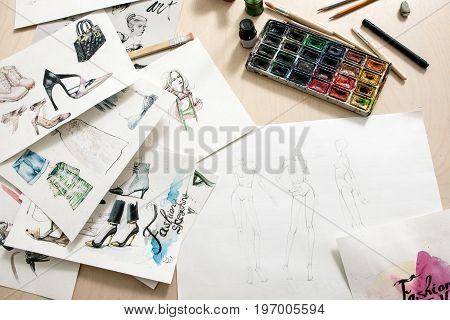 Fashion sketches on desiner desk. Art watercolor illustration of clothing creations