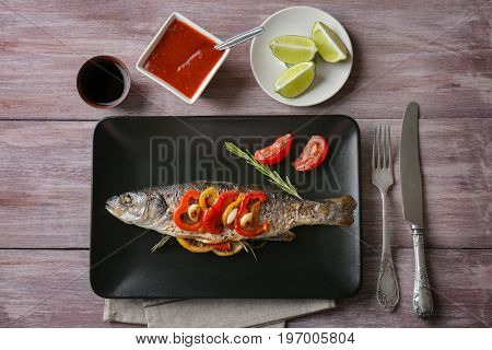 Plate with baked sea bass fish on table