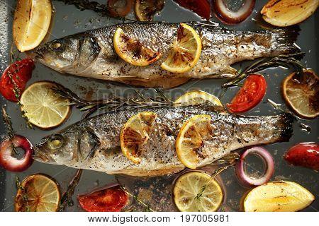 Baking pan with tasty sea bass fish and garnish, close up