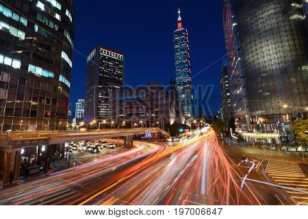 TAIPEI, TAIWAN - AUGUST 15, 2016 - Red light trails from vehicle traffic streak across a busy intersection in front of Taipei 101