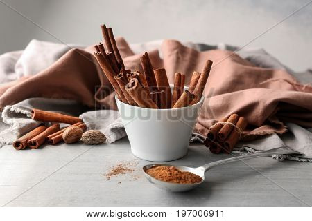 Composition with cinnamon on grey wooden table