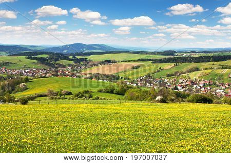 panoramic view of Horni Lidec village with meadow ful of dandelions and beautiful clouds - Carpathiam mountains - Czech Republic
