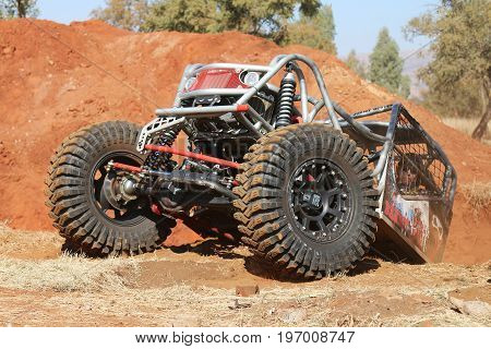 Red Car Climbing Out Steep Dugout, Front Tires Gripping On Flat Surface