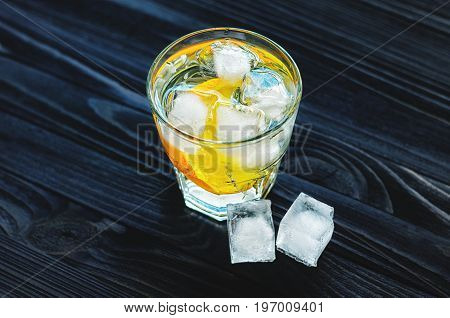 Cocktail with citrus fruits, sprig of rosemary and cubes of ice on dark wooden table