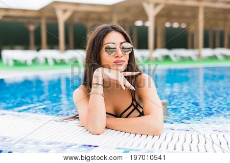 Portrait Of Sexy Cheerful Woman Relaxing At The Luxury Poolside. Girl At Travel Spa Resort Pool. Sum