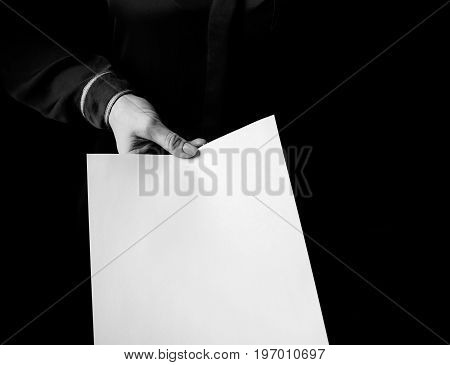 Female Hand Isolated On Black Background Giving Paper Sheet