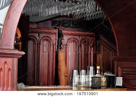 Classic Bar Counter With Bartender Accessories Shakers With Leather Apron Of Bartender Hanging On Wo
