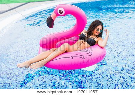 Girl On A Pink Flamingo In The Pool In Sunglasses. Summer Vocation.
