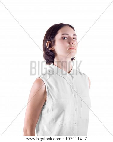A disappointed office lady isolated over the light background. A pretty girl is judging and strict. A serious young woman with a stylish black haircut wearing a white casual blouse.