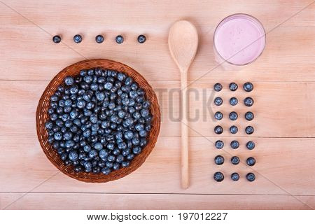 A view from above on dark purple blueberries in a wicker basket and a wooden spoon. Perfectly organized fresh blueberries and a glass of nutritious vegan smoothie on a light wooden background.