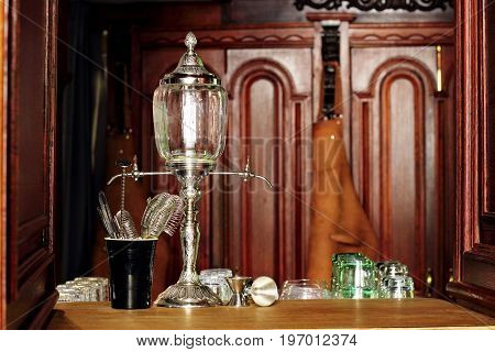 Barman equipment on bar.Absinthe Fountain.Leather apron bartender on second plan defocussed
