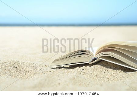 Close up of open book on the beach on warm yellow sand with ocean in the distance. Turn the page and relax.