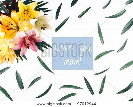 Beautiful lilies with leaves on white background. Top view with inscription Love you mom.