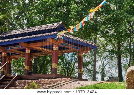 Beautiful landscape with a alcove for meditations a path trees on a sunny summer day. The site of the Tibetan culture and nature in the National Botanical Garden (Kiev Ukraine)