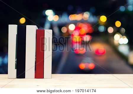 stack book on desk no labels blank spine with blurred night light bokeh background selective focus education back to school and business concept color tone effect copy space