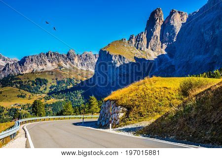 Picturesque road among the rocks on the Sella Pass. Windy sunny autumn day. Travel to South Tyrol, Dolomites. The concept of extreme and ecological tourism