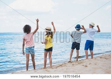 Back View Of Group Of Kids Throwing Stones At Seaside Together