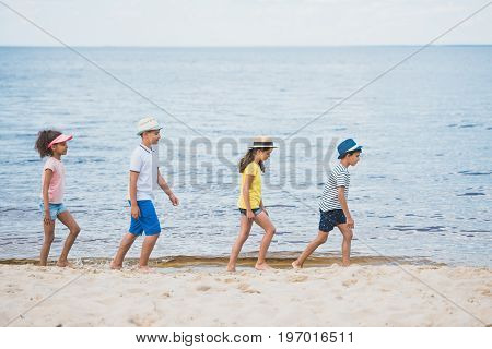 Side View Of Multicultural Kids Walking On Beach Together