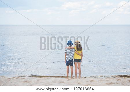 Back View Of Girl And Boy Hugging Each Other While Standing At Seaside