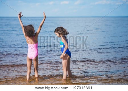 cute little girls in swimsuits playing at seaside together
