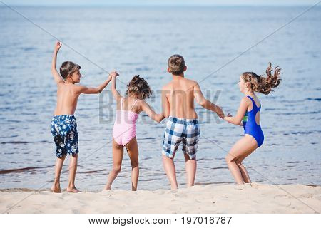 Rear View Of Group Of Little Children Holding Hands While Standing On Sandy Beach