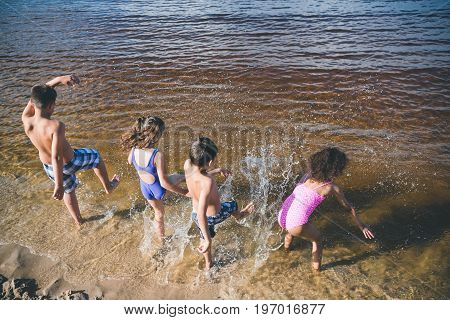 Back View Of Group Of Little Kids In Swimsuits Playing At Beach
