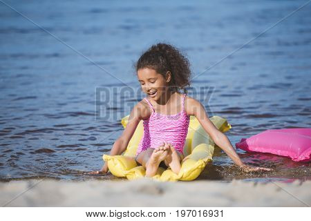 Smiling Little African American Girl Resting On Inflatable Mattress At Seaside