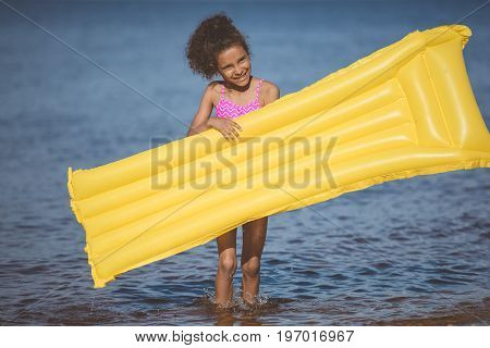 Smiling African American Girl Holding Inflatable Mattress At Seaside