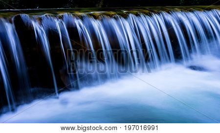 small blue waterfall on mountain river