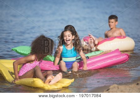 Happy Little Kids Have Fun On Inflatable Mattresses At Seaside